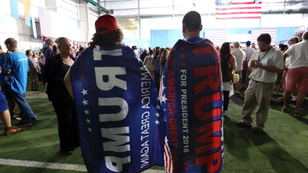 Two Trump supporters are pretty much ignored as they wear Donald trump capes at a campaign rally for Democratic ...