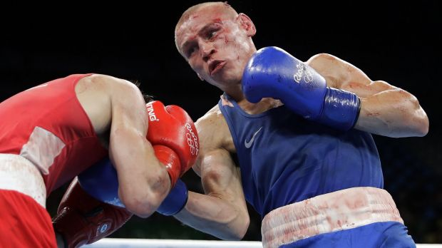 Russia's Vladimir Nikitin, right, is bloodied and bruised during his fight with Michael Conlan.