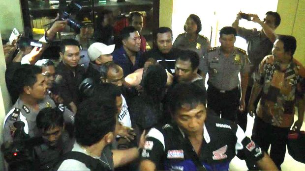 Handcuffed, David Taylor arrives at Denpasar police station on Friday.