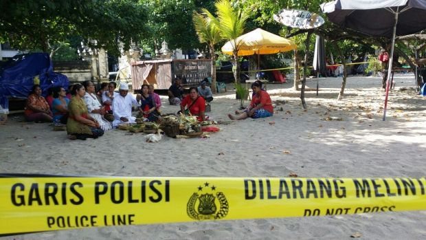 Family of the slain police officer hold a Ngulapin cleansing ceremony on Kuta beach.