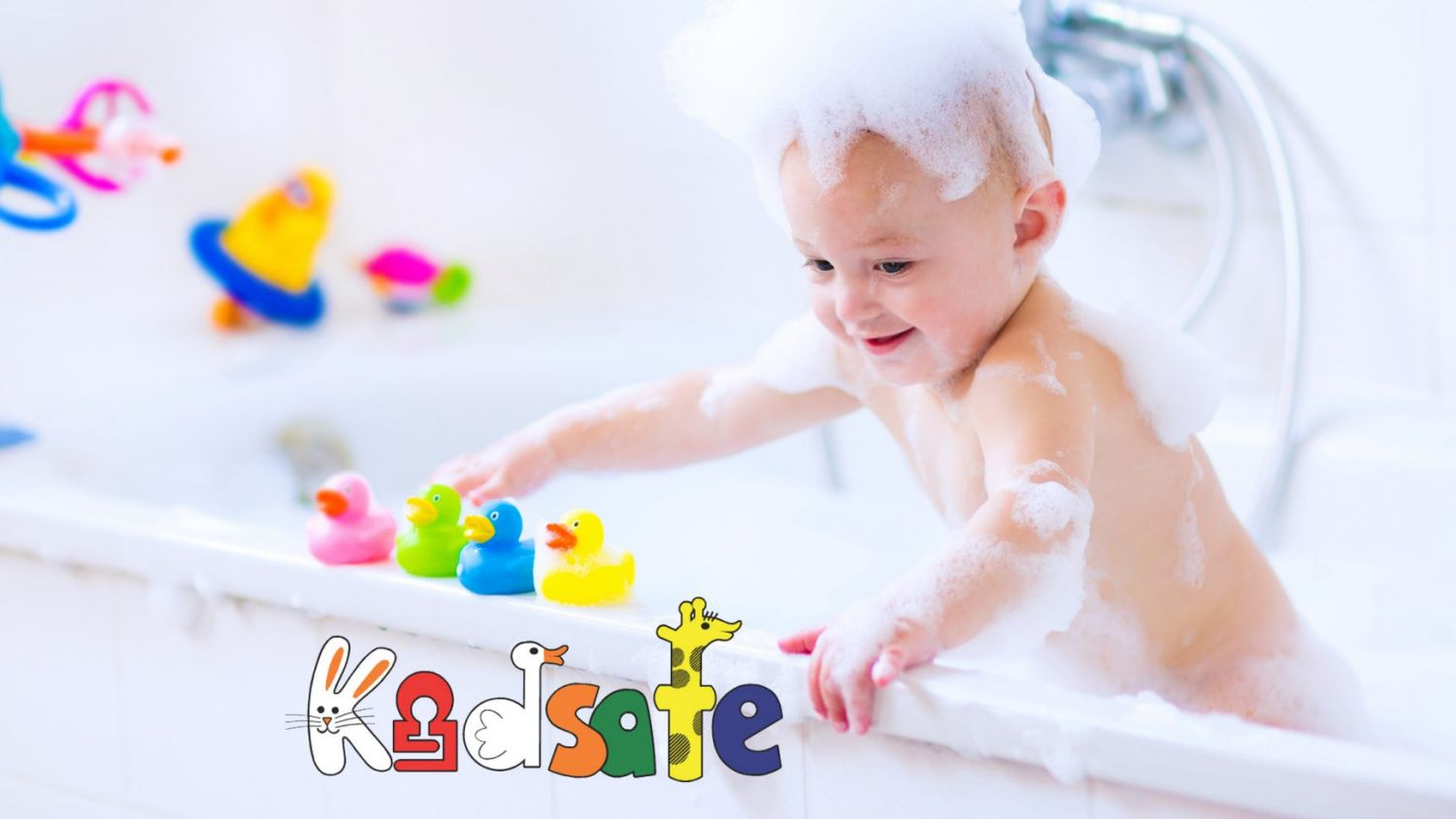 Cute little baby boy taking bath playing with foam and colorful rubber duck toys in a white sunny bathroom