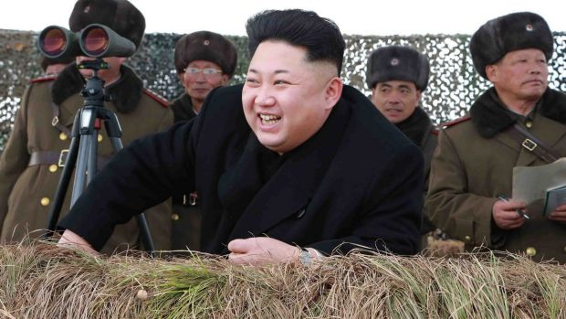 North Korean leader Kim Jong-un laughs as he watches a winter river-crossing attack drill.
