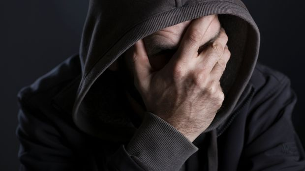 Depressed man looking despaired, hiding face with hand and hood, isolated on black background.