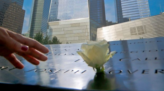 A visitor reaches out to touch a name engraved on the September 11 memorial in New York.