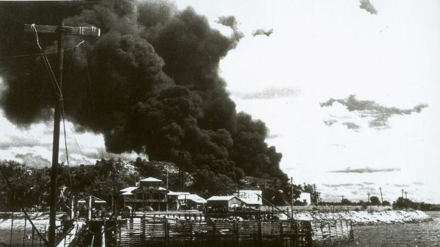 Darwin, 19 February 1942. People at Government House look at the smoke billowing from ships ablaze in the harbour after ...