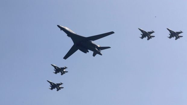 US B-1 bomber, centre, flies over Osan Air Base, South Korea, accompanied by jet fighters.