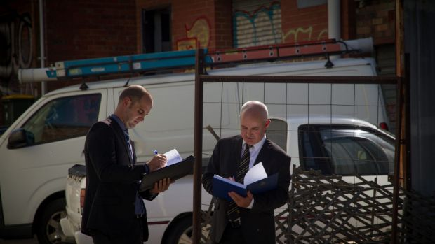 Paul Rowe (left) and Dave Butler typify the public's idea of homicide squad detectives, carrying bound folders and ...