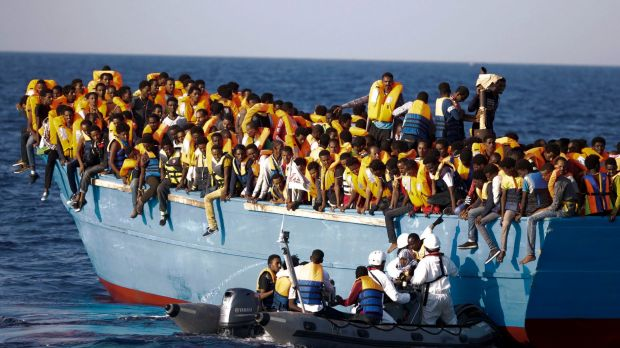 Italian officers rescue a woman from a crowded wooden boat carrying more than seven hundred migrants, during a rescue ...