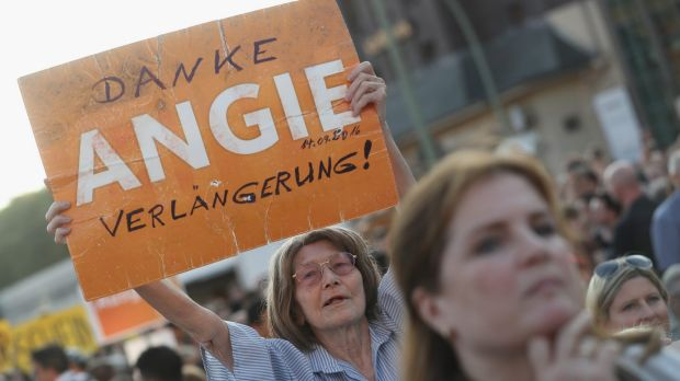 """A supporter of the German Christian Democrats holds up a sign that reads: """"Thanks Angie, keep going!"""" in reference to ..."""