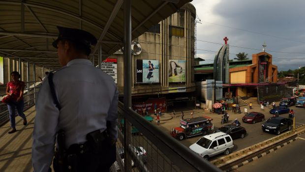 A police officer stands on the overpass connecting two malls in Cagayan De Oro where two of Peter Scully's victims were ...