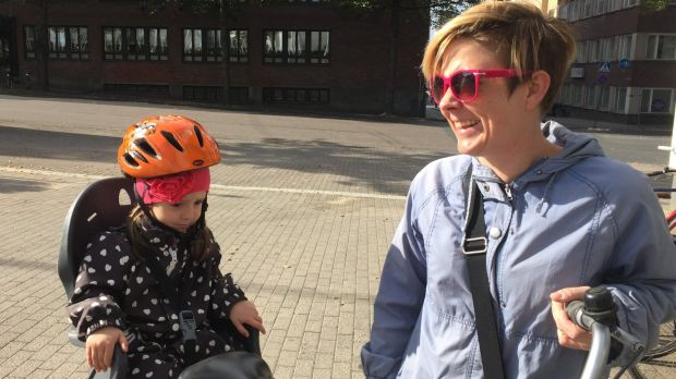 A Finnish mother is embarrassed that she hasn't got a bike helmet, but her daughter is wearing one.