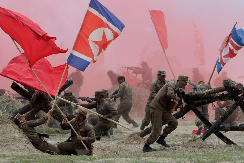 South Korean soldiers wear North Korea's military uniforms and hold North Korea's flags, acting as North Korean ...