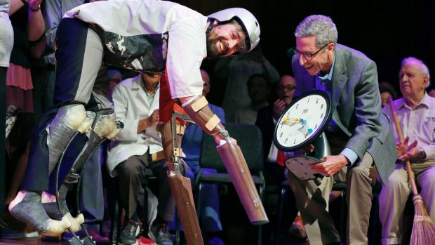 Thomas Thwaites, left, accepts the Ig Nobel prize in biology from Nobel laureate Eric Maskin while wearing his goat ...