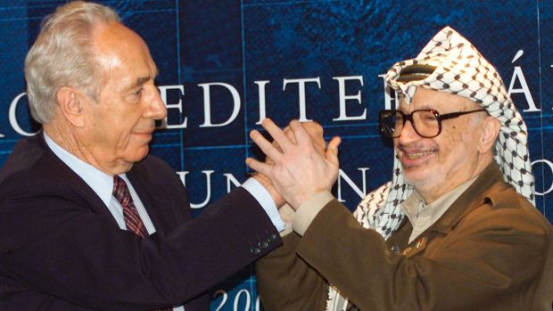 Palestinian leader Yasser Arafat, right, clasps hands with then Israeli Foreign Minister Shimon Peres, left, at a ...