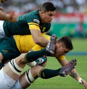 Australia's Sean McMahon, centre, feels the full force of the Springboks.