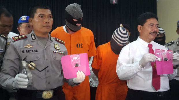 Police with Australian Giuseppe Serafino (in orange prison clothes, right) and Briton David Fox, after their arrest in ...