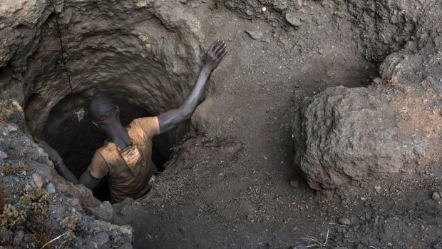 "A ""creuseur"" descends into a tunnel at the mine in Kawama. About 100,000 cobalt miners in Congo use hand tools to dig ..."