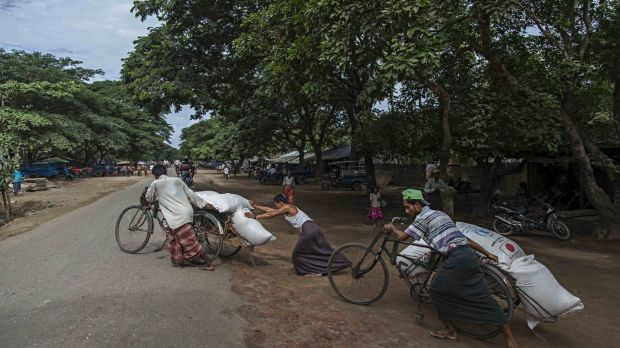Rohingya men prepare to deliver rice donations from the World Food Program in Sittwe in May.