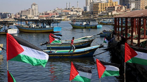 A Palestinian walks on a boat decorated with national flags as he awaits the arrival of the 13 pro-Palestinian female ...