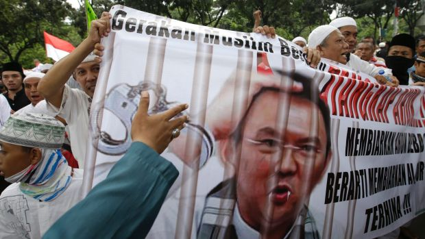 Muslim protesters hold a banner calling for the arrest of Jakarta Governor Basuki Tjahaja Purnama, popularly known as ...