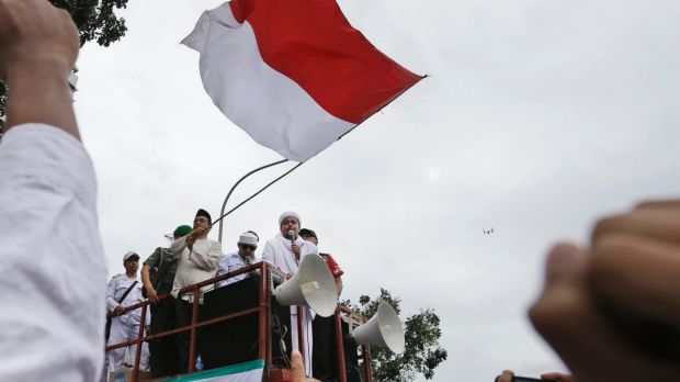 Muslim protesters raise their fists as the leader of Islamic Defenders Front, Rizieq Shihab, gives a speech during a ...