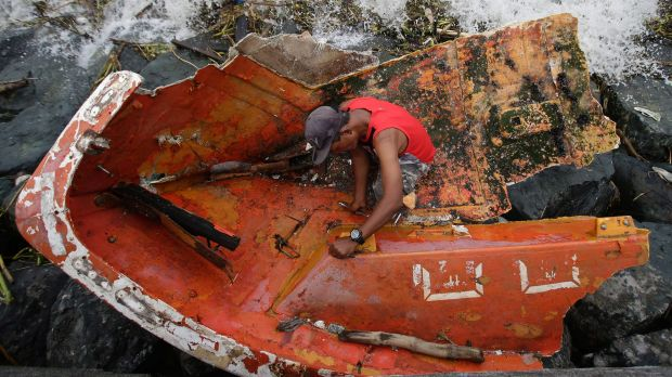 Filipino Joybin Marayo, 58, salvages metals on a damaged boat that was washed ashore by strong waves brought about by ...