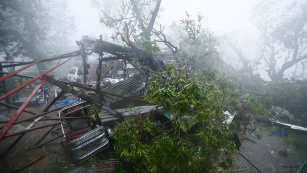 A tricycle is pinned by tree branches at the height of super typhoon Haima that lashes Narvacan township, Philippines.