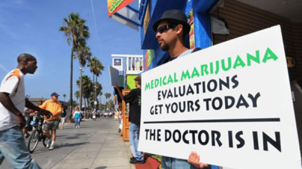 Dispensations ... a man holds a placard at a clinic at Venice Beach, Los Angeles. Critics say some doctors will ...