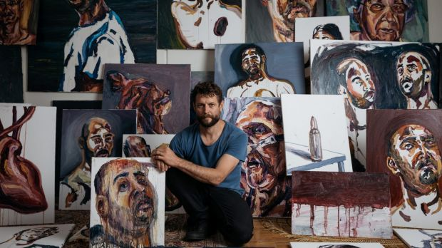 Artist Ben Quilty surrounded by works painted by Myuran Sukumaran while on death row.