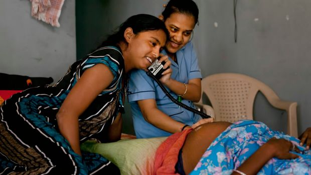A nurse and a surrogate mother listen to a baby's heartbeat in a dormitory run by Akanksha Clinic, in Anand, India prior ...