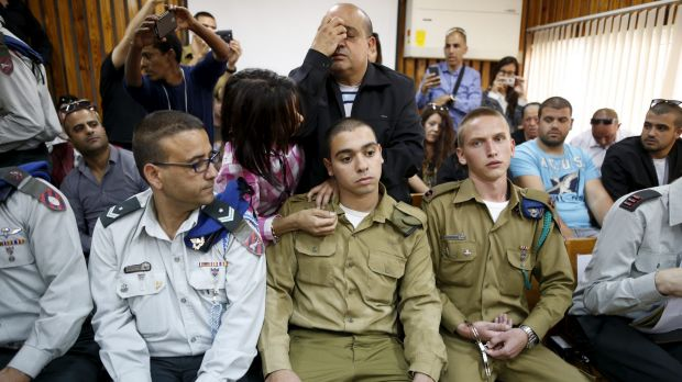 Israeli soldier Elor Azaria, centre seated, in court charged with manslaughter by the Israeli military. His father prays ...