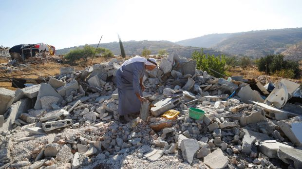A Palestinian inspects the rubble of a family home demolished by Israeli troops in the occupied West Bank village of ...