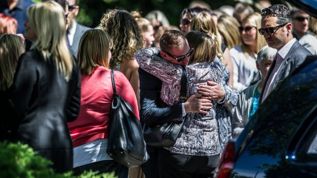 David Turner, partner of Kate Goodchild being comforted outside the funeral of siblings Kate Goodchild and Luke Dorsett.