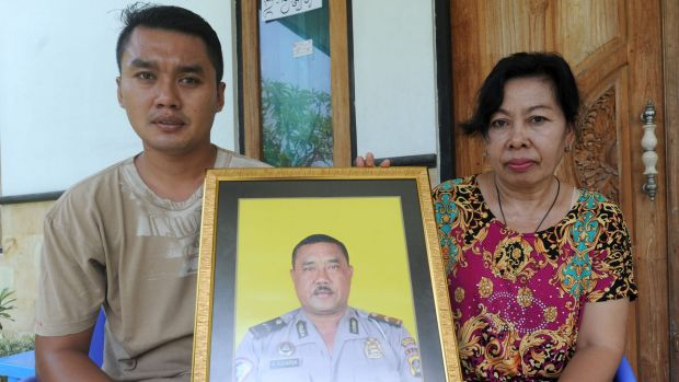 The widow of Wayan Sudarsa, Ketut Arsini, and her son Kadek Toni, hold a portrait of the police officer who was killed ...