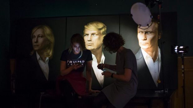Two women wait in front of portraits of Marine Le Pen, Donald Trump and  Vladimir Putin for a live telecast of election ...