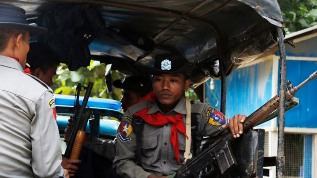 Myanmar police officers sit in a truck as they provide security in Maungdaw, Rakhine State, Myanmar.