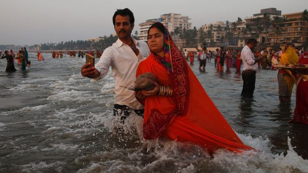 A man takes a selfie with his wife as she offers prayers to the Sun at the Arabian Sea during Chhath Puja festival in ...
