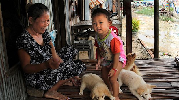 A woman plays with a child in Khmounh, Cambodia, where dozens of women have signed surrogacy agreements to bear children ...
