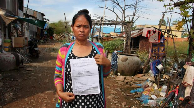 Cambodian surrogate mother Hour Vanny, holding the two-page document she signed with Fertility Solutions, operated by ...