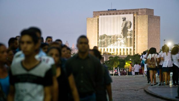 A photograph of the late Fidel Castro hangs on a building in Revolution Plaza, Havana, where people wait in line to pay ...