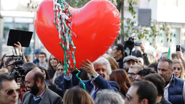 Five Star Movement leader Beppe Grillo holds a heart-shaped balloon adorned with strips in the colours of the Italian ...