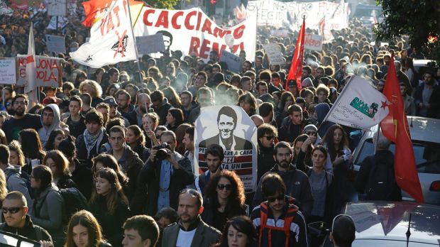 """People march behind a banner portraying Italian premier Matteo Renzi that reads """"Let's oust Renzi"""" during a ..."""