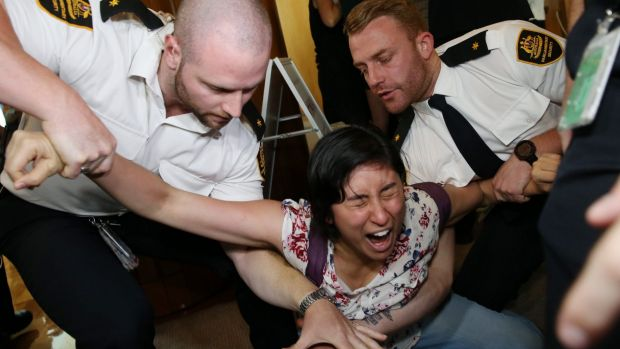 Woman screams as she's removed from Parliament House in Canberra on Wednesday.
