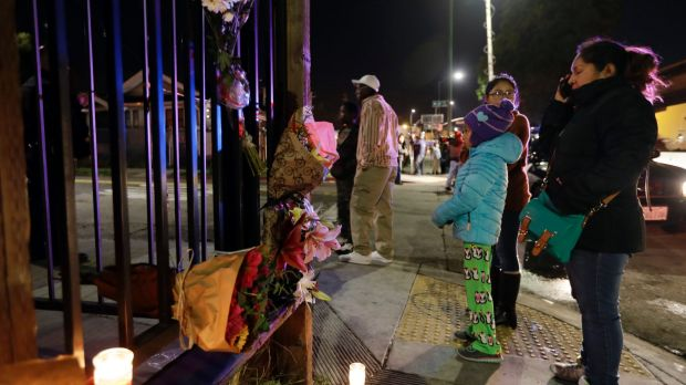 Flowers and candles are placed at the site of the California warehouse fire on Saturday.