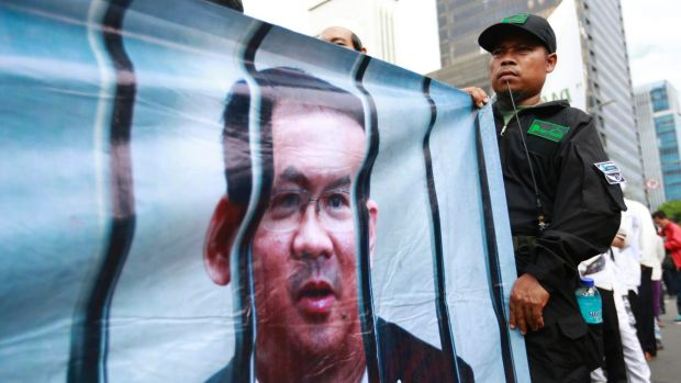 A Muslim protester displays a banner depicting Jakarta governor Ahok behind bars outside court on the day of his trial ...