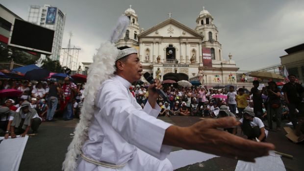 A protester dressed as a priest performs during a Christmas-theme street play to protest alleged extra-judicial killings ...