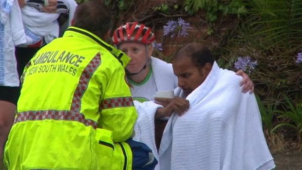 An ambulance officer comforts cyclists after a woman was killed on Mona Vale Road, Pymble.