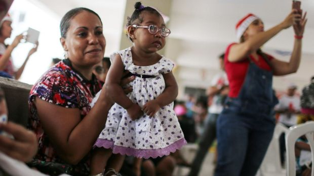 Ana Livia, centre, who was born with microcephaly, is held by her mother Janaina during a Christmas party in support of ...