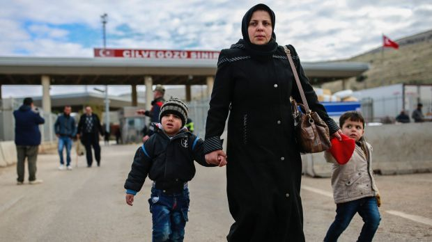 Iptisam Muhammed, 25, from Aleppo, walks with her children across the Turkish border on Sunday.