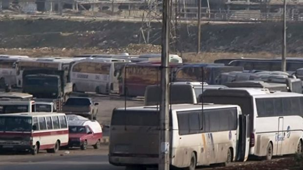 In this still image taken from Syrian TV, buses line up to cross into east Aleppo on Sunday.